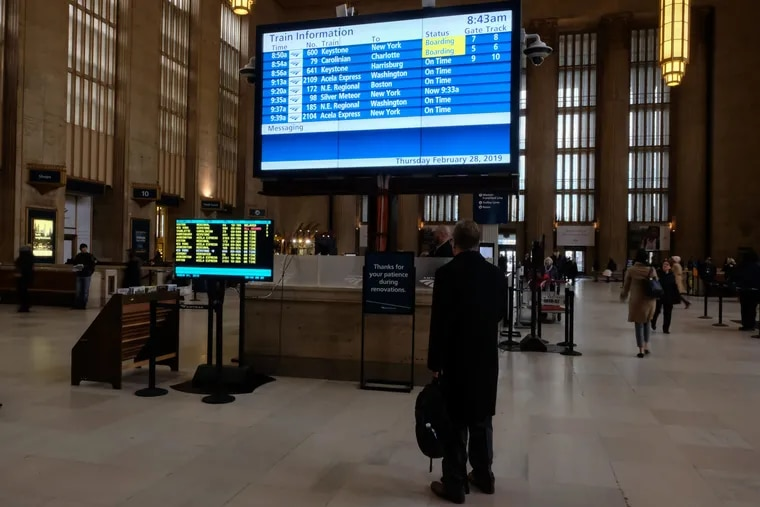 An Amtrak passenger checks the new digital schedule board at 30th Street Station.