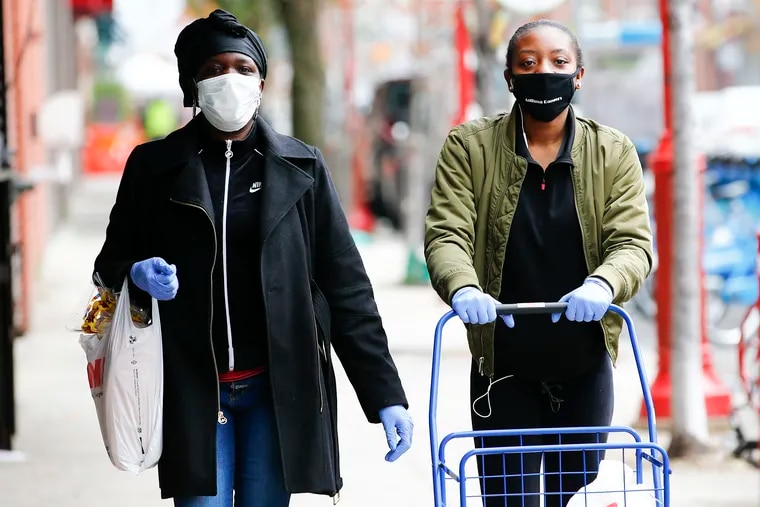 Two women walk along South Street wearing masks on Monday, March 30, 2020. Some experts are increasingly encouraging Americans to wear masks while out in public.