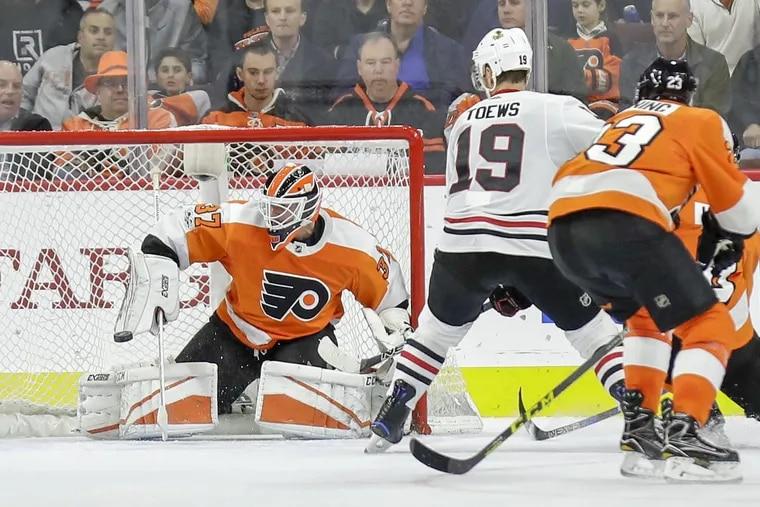 Flyers' goalie Brian Elliott stops the puck against Blackhawks center Jonathan Toews during the Flyers' 3-1 win.