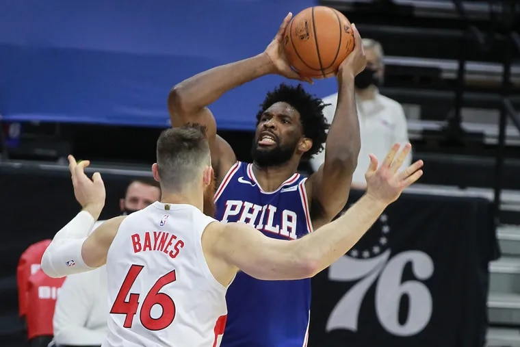 Joel Embiid, right, of the SIxers shoots over Aron Baynes of the Raptors during the 1st half of a NBA game at the Wells Fargo Center on Dec. 29, 2020.