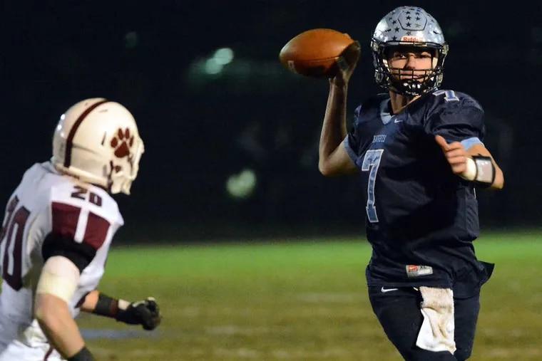 North Penn quarterback Reece Udinski ,7, scrambles away from Garnet Valley defender Dave Wood ,20. Mark C Psoras