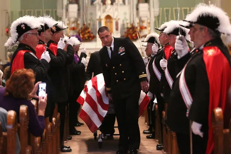 Lt. Brian Lewis escorts the casket before the Mass of remembrance for Chaplain Aloysius Schmitt on Wednesday, Oct. 5, 2016, at St. Luke's Church in St. Lucas, Iowa. Schmitt is scheduled to be honored with the Silver Star medal Thursday.