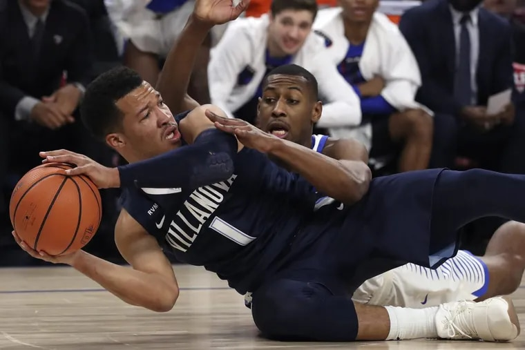 Villanova's Jalen Brunson tries to keep the ball from DePaul's Brandon Cyrus during the first half of an NCAA college basketball game Wednesday, Dec. 27, 2017, in Chicago.