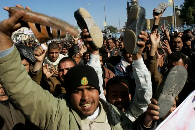 Iraqis raise their shoes as hundreds demand the release of Iraqi journalist Muntadhar al-Zeidi, who threw his shoes at President Bush on Sunday.