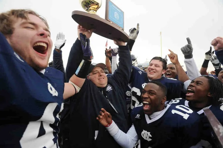 West Catholic head coach Brian Fluck hoists the Class AA state championship trophy, surrounded by his jubilant players.