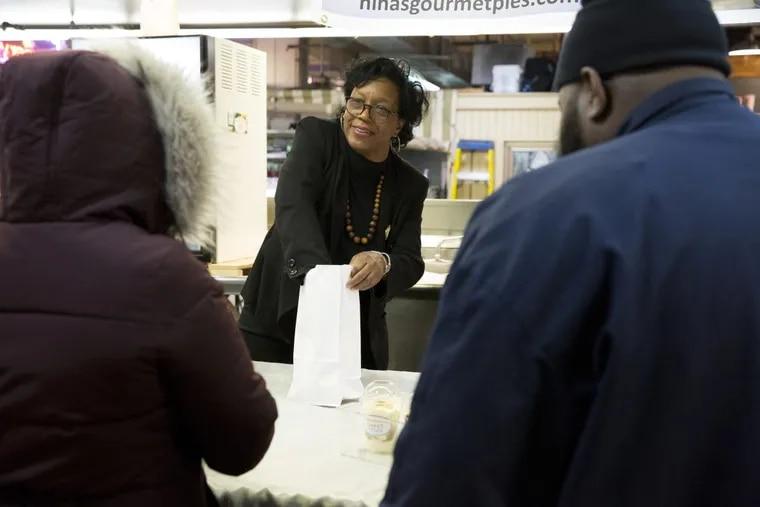 Owner Nina Bryan sells Sweet Nina's banana pudding from a day stall/cart at Reading Terminal Market.