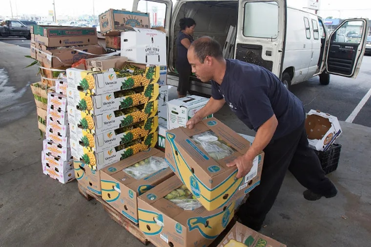Customers load fruits and vegetables into a van at The Philadelphia Wholesale Produce Market in Southwest Philadelphia.