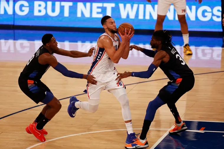 76ers guard Ben Simmons drives to the basket between Knicks center Nerlens Noel (right) and guard RJ Barrett Saturday.