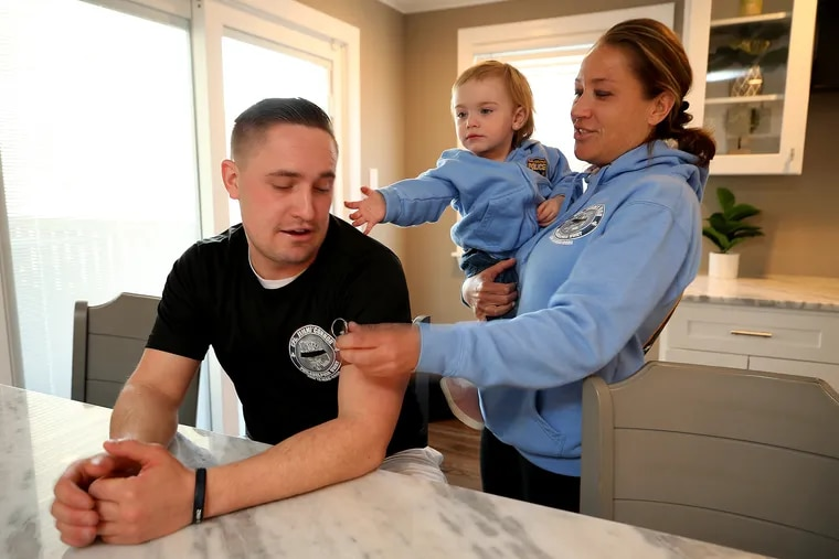Philadelphia Police Officer Jimmy O'Connor (left) talks about his late father as his mom, Terri O'Connor, holds his daughter, Callie, at her Northeast Philadelphia home on Thursday.