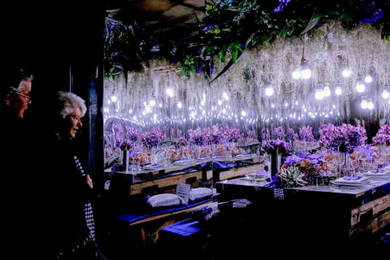 Bob and Maureen McCook of West Chester peek inside one of the cargo-container displays, multi-flowered with complementary lighting.