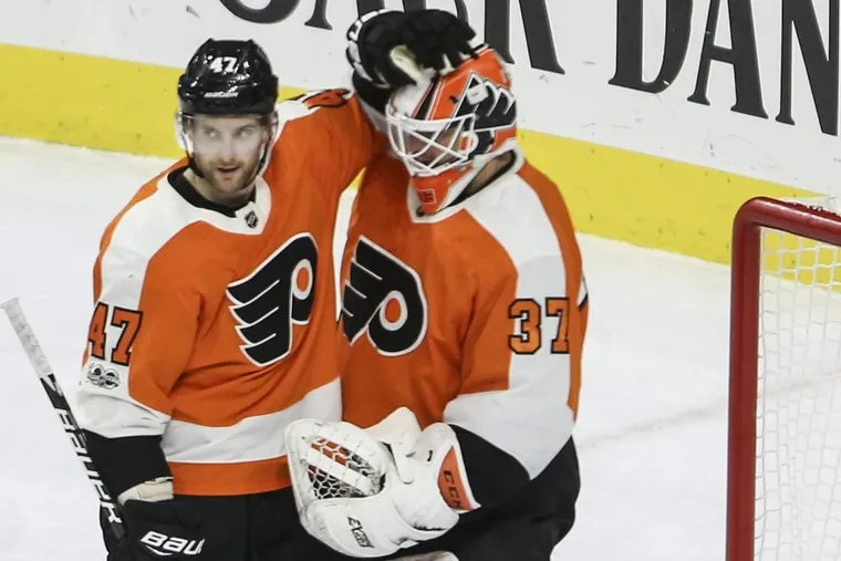 Andrew MacDonald celebrates with goalie Brian Elliott after a recent Flyers win. The NHL named Elliott the No. 2 star of the week.