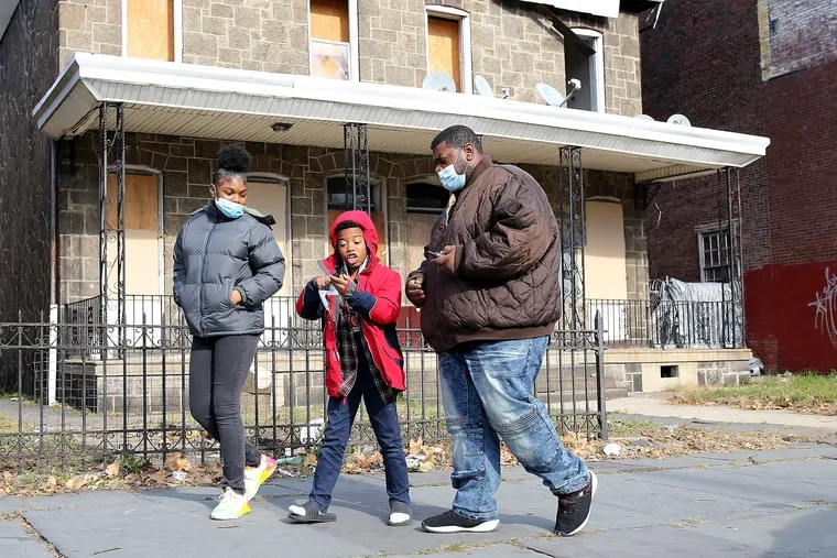 B.J. (center) talks with his father, Benjamin, as his sister, Renee, watches during a walk along Lehigh Avenue. The Todds live at the Lutheran Settlement House on Lehigh Avenue.