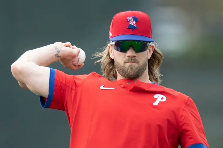 Bryce Harper plays catch Wednesday during the Phillies' spring-training workout in Clearwater, Fla.