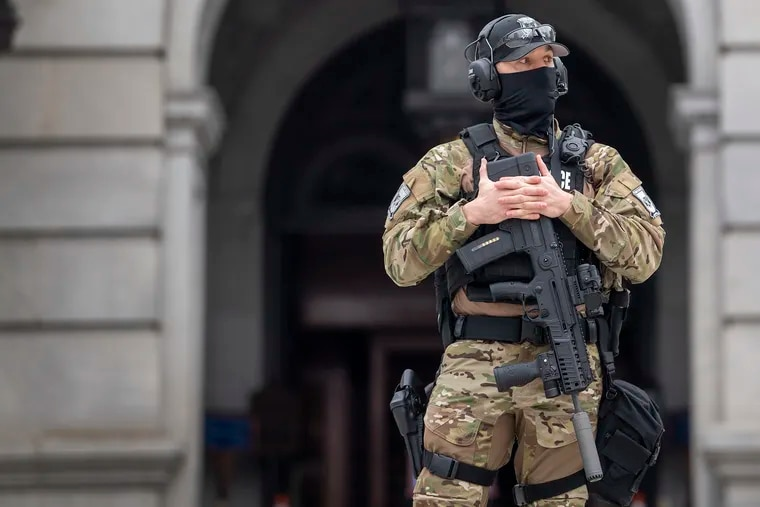A member of the Pennsylvania Capitol Police guards the entrance to the Pennsylvania Capitol Complex in Harrisburg on Jan. 13. State capitol buildings across the country are under heightened security after the siege of the U.S. Capitol last week.