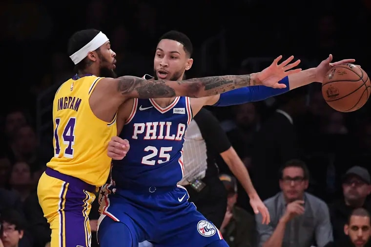 Los Angeles Lakers forward Brandon Ingram finds he can't take the ball away from Ben Simmons during the first half at the Staples Center.