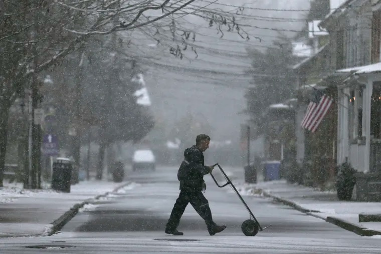 A delivery man makes his way through wintry weather in Mt. Holly, N.J., on a snowy day last year.