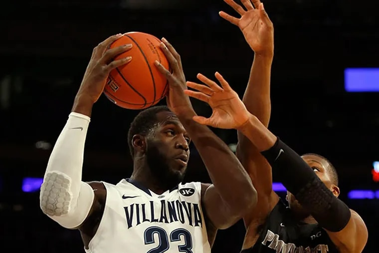 Villanova's Daniel Ochefu grabs a rebound past  Providence' Kris Dunn during the first half in the 2015 Big East Men's Basketball Championship semifinals on Friday, March 13, 2015 at Madison Square Garden in New York. (Yong Kim/Staff Photographer)