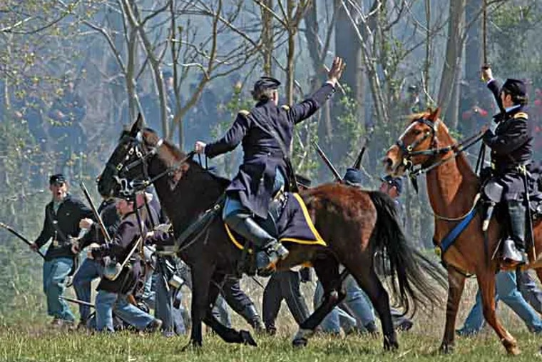 GETTYSOLDIERS30-f - Sirlin on horseback on the right hand, looking away from the camera with his sword in hand, extended to the sky. The photos are provided courtesy of Jon Sirlin, who is a Philadelphia lawyer, planning to take part in the big Gettysburg reenactment. The photos are generally taken at recent reenactments or living history demonstrations.