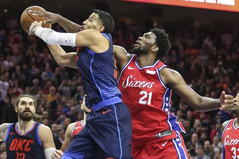 Sixers' center Joel Embiid knocks the ball away from Thunder guard Andre Roberson on Friday.