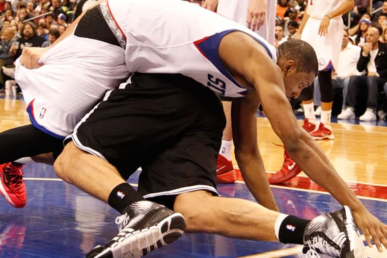 Thaddeus Young (top) fouls the Nets' Brook Lopez. (Ron Cortes/Staff Photographer)