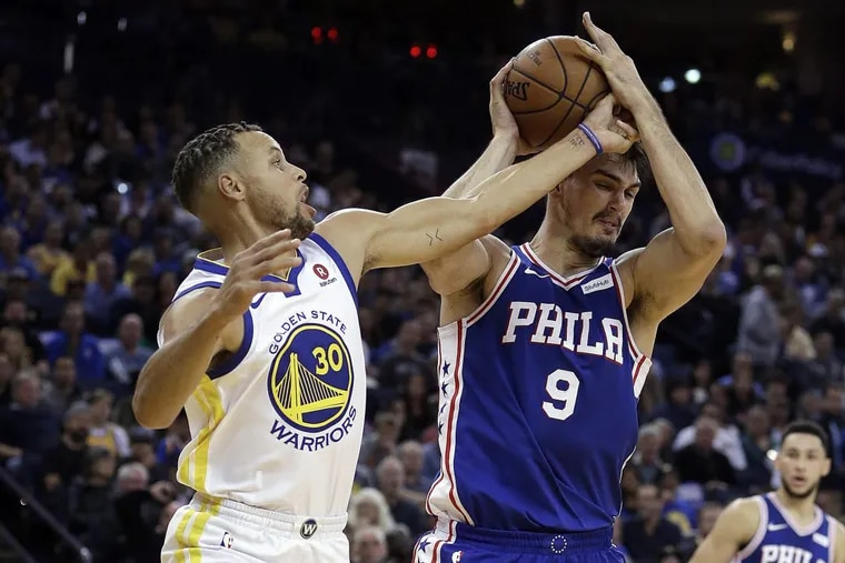 The Sixers' Dario Saric (right) keeps the ball from Golden State's Stephen Curry on Saturday, Nov. 11, 2017.
