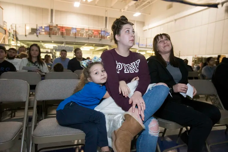 Melanie Klein, left, hugs her mother Nicole Flanagan, center, as they realize Melanie did not get a kindergarten spot at MaST Community Charter School during the school's lottery Tuesday. Nicole's mother, Shannon Flanagan is right.