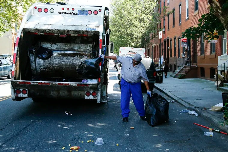 A City of Philadelphia sanitation worker prepares to toss trash into a garbage truck along the 1700 block of Diamond Street near the Temple University campus earlier this month.