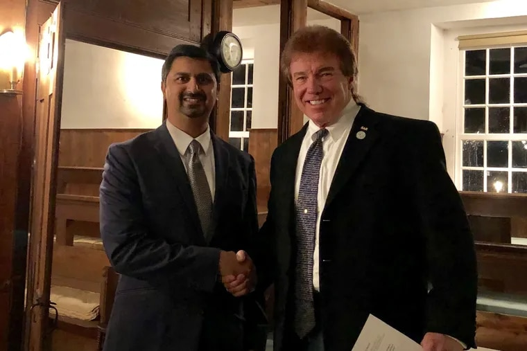Chesterfield Township Committeeman Shreekant Dhopte (Left) and former Committeeman Sam Davis (right) shake hands at the Crosswicks Friends Meeting in Chesterfield Tuesday night.
