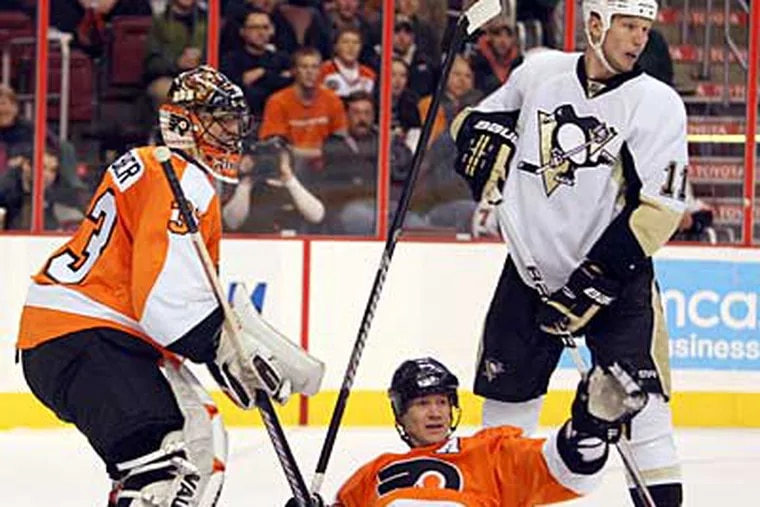 Chris Pronger (center) hits the ice between Brian Boucher (left) and Penguins' Jordan Staal. (Yong Kim / Staff Photographer)
