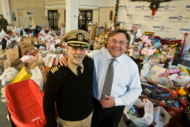 With a backdrop of thousands of toys, Capt. Howard Stephen Serlick, of the Naval Reserve, and Brian Tierney, chief executive of Philadelphia Media Holdings, pose in PMH's lobby yesterday.