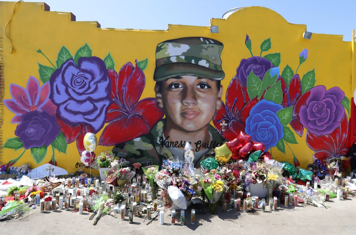 Offerings sit in front of a mural of slain Army Spc. Vanessa Guillen painted on a wall in the south side of Fort Worth, Texas. U.S. Army officials say they will begin an independent review of the command climate at Fort Hood, examining claims and historical data of discrimination, harassment, and assault.