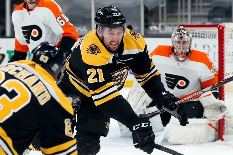The Boston Bruins' Nick Ritchie (21) digs for the puck against the Flyers during the second period as goalie Carter Hart braces for a shot on Saturday. Boston cruised to a 6-1 win.