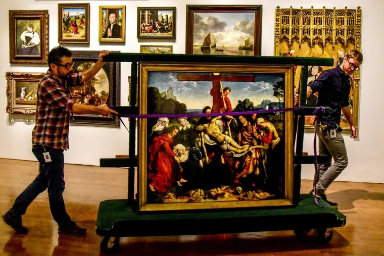 """Installation technicians Hiro Sakaguchi (left) and Noah Yoder wheel Joos van Cleve's 1518 painting """"Descent from the Cross"""" through the exhibition space at the Philadelphia Museum of Art."""