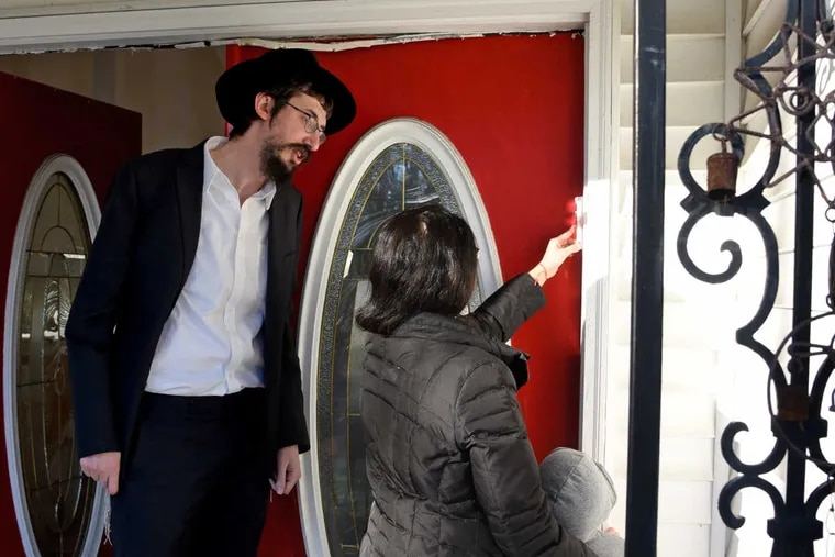 Rabbi Menachem Kaminker (left) helps Noa Nidam and her son Aerial place a mezuzah on her front doorway. After threats and a sharp rise in anti-Semitic incidents across the United States there is now an effort to place mezuzahs on the doors of Jewish homes in  South Jersey neighborhoods, including Cherry Hill, where rabbis are going door to door.