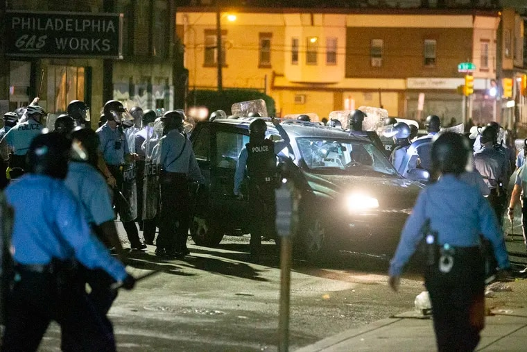 Police surround a vehicle on Chestnut St. between 52nd and 53rd streets just before 2 a.m. on Tuesday morning during unrest in West Philadelphia.