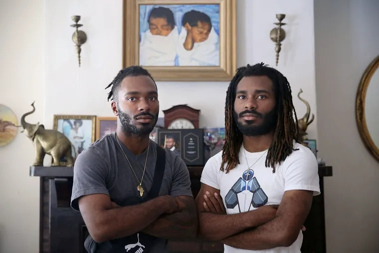 Twins Julian, left, and Julius Whitehead, who were both shot in 2018, stand for a portrait at their home in Philadelphia's Harrowgate section.