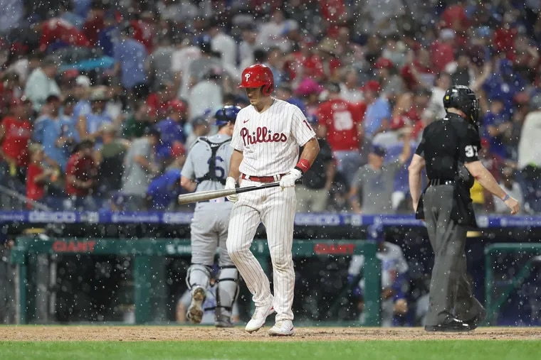 Phillies catcher J.T. Realmuto walks back to the dugout as Tuesday night's game against the Dodgers is delayed in the fourth inning because of rain and lightning.