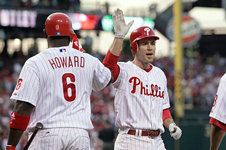Philadelphia Phillies Ryan Howard congratulates Chase Utley on his two-run home run against the Florida Marlins at Citizens Bank Park in Philadelphia Friday night. (Jerry Lodriguss / Inquirer)