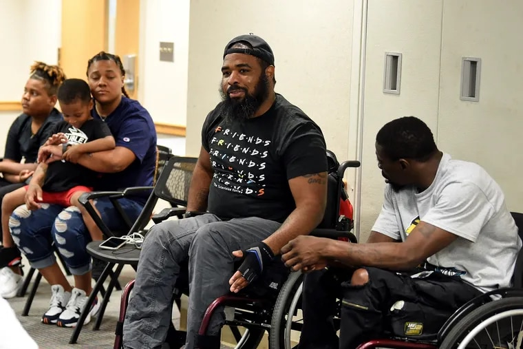 Paralyzed gunshot survivors Tyrone Shoemake (left), John Muldrow (right) and Jalil Frazier (center) get together for the first time to talk about creating a support group at Temple University Hospital July 15, 2019. Frazier is part of an online community but came up with the idea of a fellowship of survivors to meet others in person. His fiancé Tamira Brown (rear) and their boys, Jaylin Frazier-Brown 4, and Jaymere Perry-Brown , 11, also attended, along with friends and family of the other survivors.