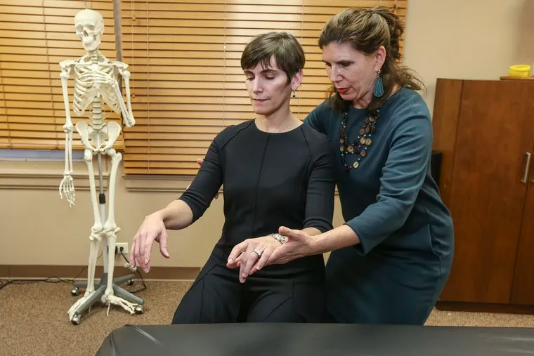 Ariel Weiss teaches the Alexander Technique, a way of thinking about body mechanics that can reduce pain. Here Weiss works in her Center City office with Karen Zur, a pediatric otolaryngologist at Children's Hospital of Philadelphia who specializes in airway and voice disorders.