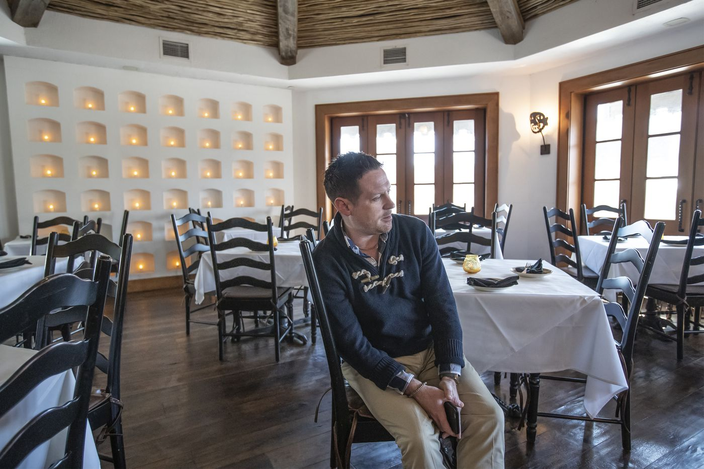 Bar manager Paul Moran, center, sits by himself in an empty Besito Restaurant in the Suburban Square shopping center in Montgomery County, Pa., on Sunday March 15, 2020.