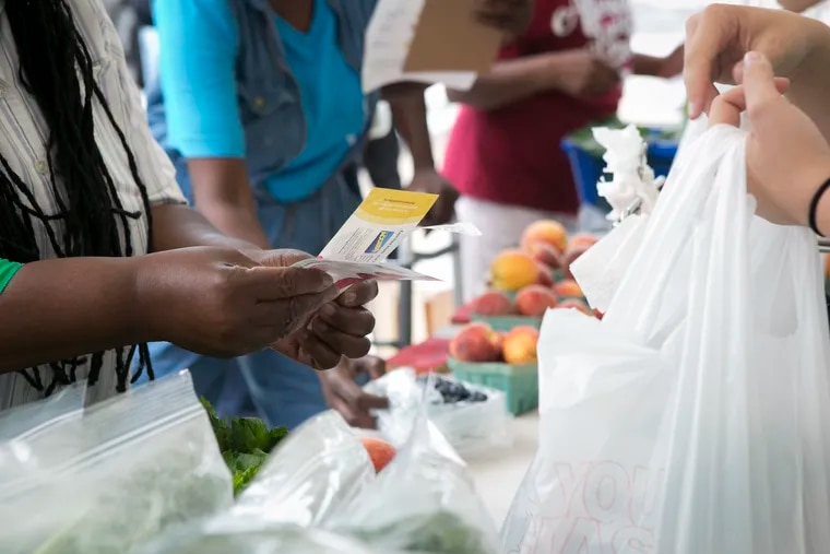 A customer uses her food bucks to pay for produce at the farmer's market at Devereaux United Methodist Church in North Philadelphia. A federal report says the war on poverty was a success.