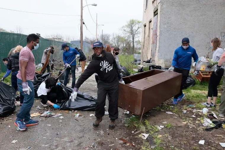 Terrill Haigler of North Phila. (center, also known as Ya Fav Trashman) guides a metal cabinet towards the trash truck during the cleanup on the 600 block of N. Hutton St. on April 10, 2021.