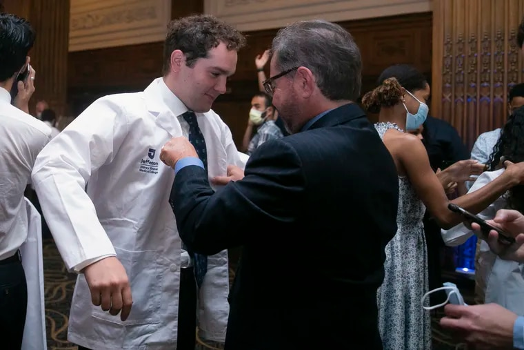 Cristian DeSimone has his white coat put on him during a ceremony for Jefferson medical school students in July. The students are beginning their medical school journey coming off the worst of the pandemic.