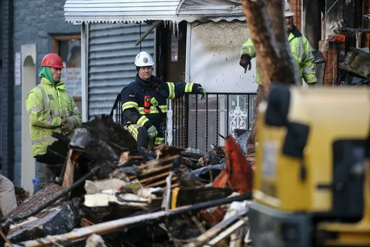 A fire marshal watches Friday as firefighters work to recover victims of the explosion and fire on the 1400 block of South Eighth Street.