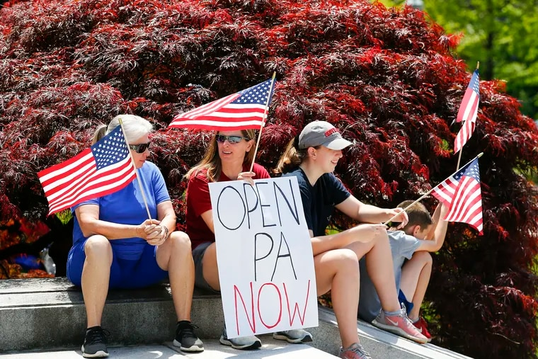 ReOpen PA supporters sit during a demonstration on the steps of the State Capital Building in Harrisburg on Friday.  The demonstration was the second anti-shutdown protesting Governor Tom Wolf's shutdowns of non-essential businesses due to the coronavirus pandemic.