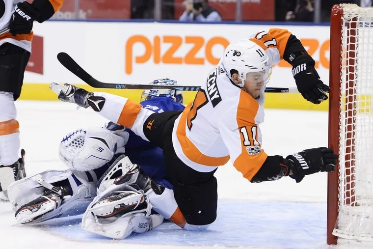 Flyers center Travis Konecny (11) crashes over Maple Leafs goalie Frederik Andersen (31) during a game Saturday.
