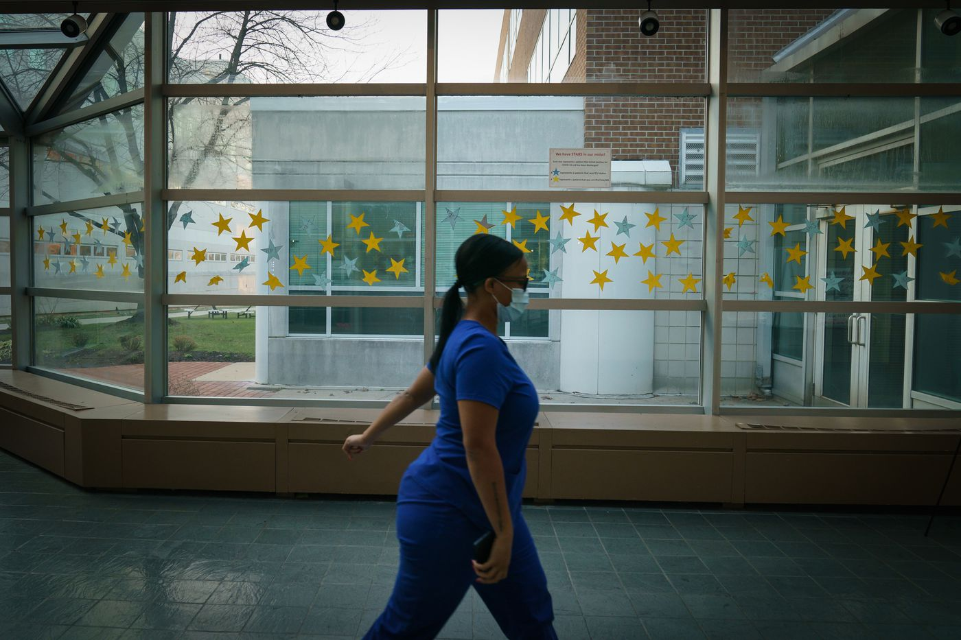 A staff person walks past a display of stars, each one representing a patient who tested positive for COVID-19 and was discharged from Suburban Community Hospital.