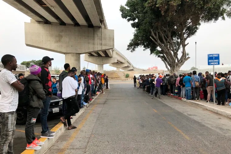 In July, a group of migrants in Tijuana, Mexico, listen to numbers being called for people to claim asylum in the U.S. The long waits are testing the patience of immigrants and border towns.