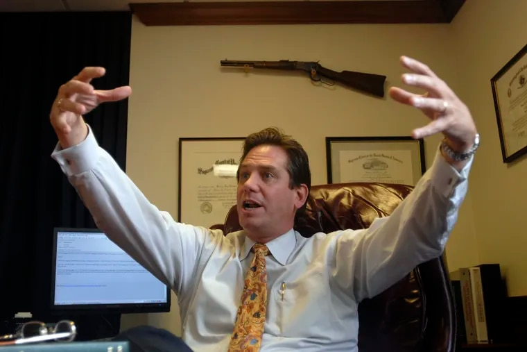 Montgomery County District Attorney Bruce Castor animates a story while being interviewed in his office at the Montgomery County County Courthouse. In the background is one of several handguns and rifles is displayed in his office.